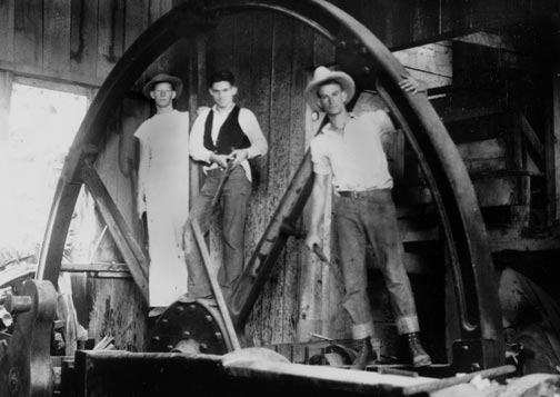 Inside the abandoned stamp mill in the late 1930's. Note the size of this size of the massive flywheel that these young adventures with their rifles are posing on. - Rick Keppler collection.