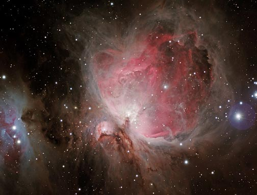 This is the nebula m42 in the constellation Orion.  It is a popular object to view with binoculars, but don't expect it to look like this.  This image is a timed exposure through a large powerful telescope.